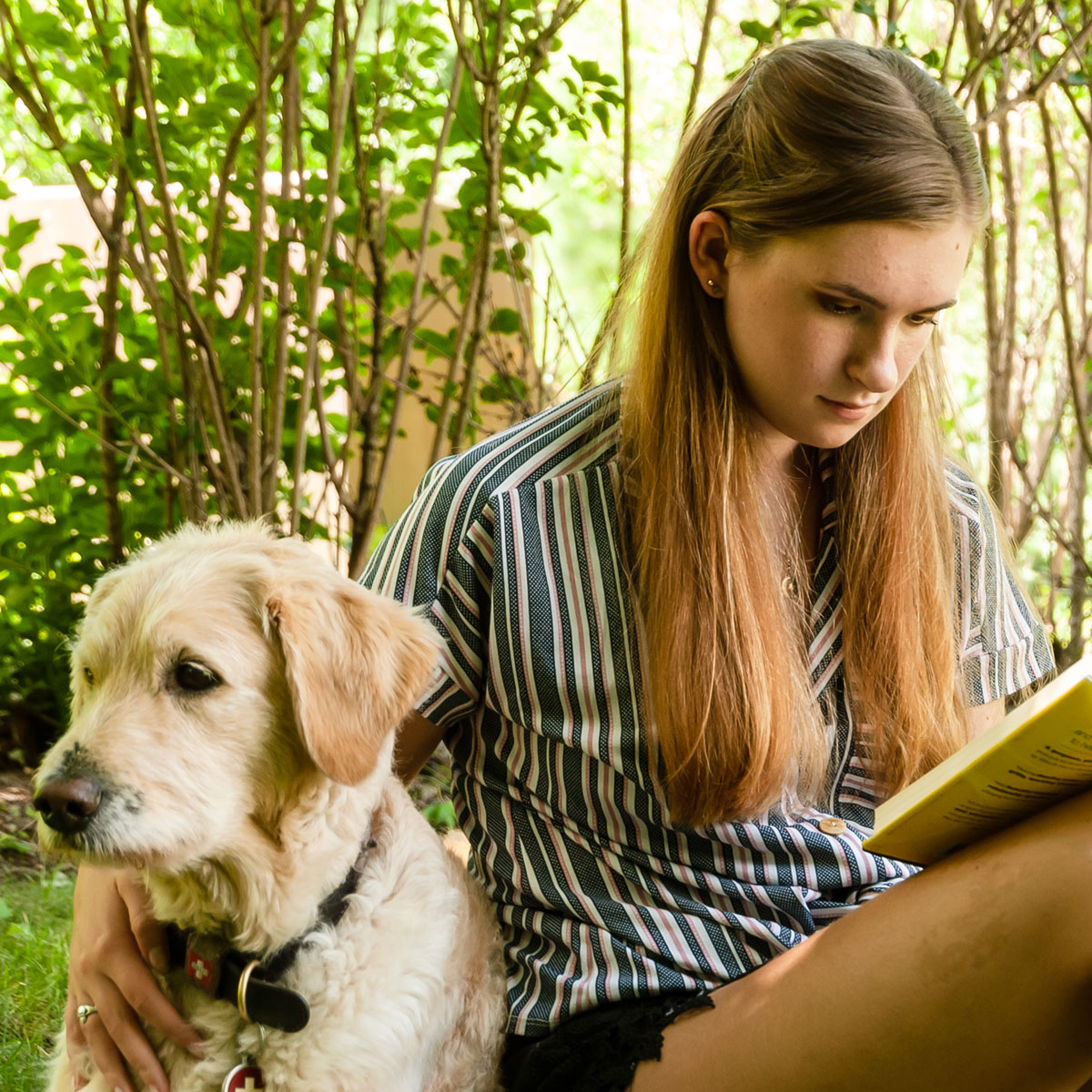 student reading with dog outside