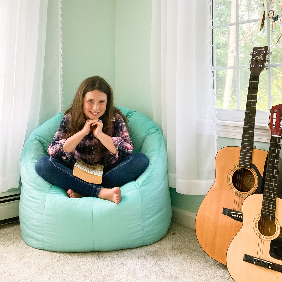 student in her room reading on beanbag chair with guitars