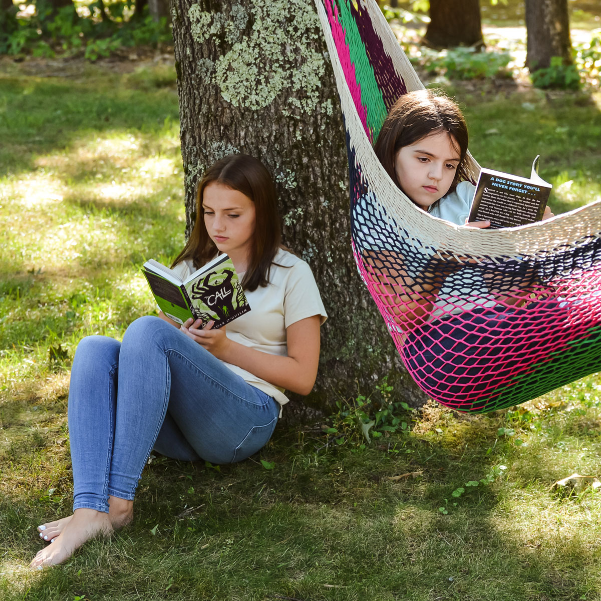 students outside in yard on grass and in hammock reading