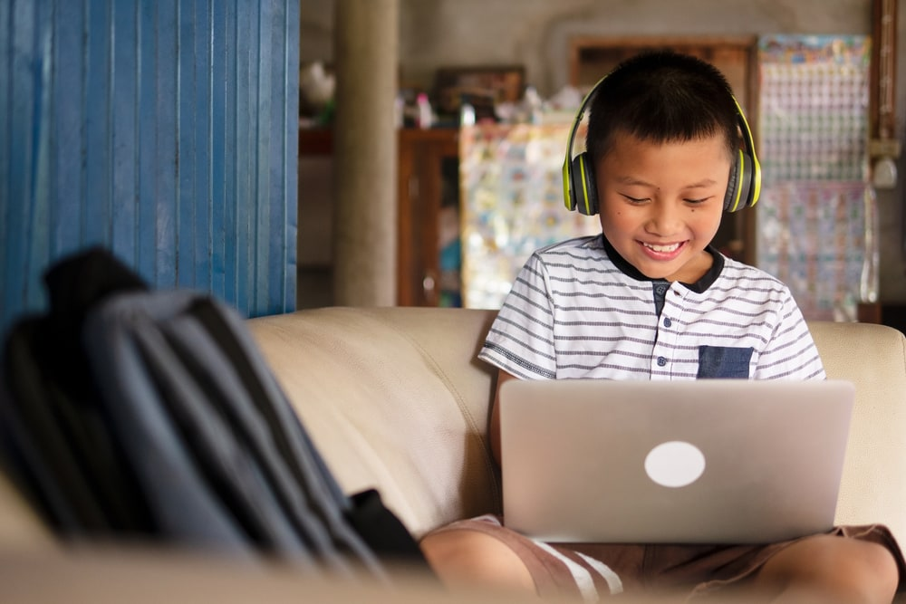 child on laptop computer with headphones smiling